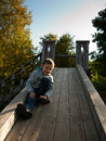 Child sitting on a wooden hill against the sky Stock Photography