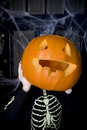 Child in a skeleton costume at a Hallowe'en party, holding a pumpkin with a carved face Royalty Free Stock Photo