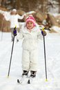 Child skiing happy girl in winterwear with her mother behind Royalty Free Stock Photos