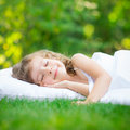 Child sleeping in spring garden happy on green grass outdoors Stock Photo