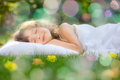 Child sleeping in spring garden happy on green grass outdoors Stock Photos