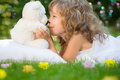 Child sleeping in spring garden happy kid with toy teddy bear on green grass outdoors Royalty Free Stock Photography