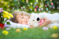 Child sleeping in spring garden happy with toy teddy bear on green grass outdoors Stock Images