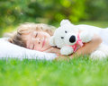 Child sleeping in spring garden happy with toy teddy bear on green grass outdoors Royalty Free Stock Photos