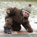 Child on slippery pavement winter or sidewalk trying to stand up after falling down Royalty Free Stock Photos