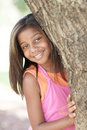 Child smiling from behind the tree Stock Image