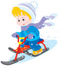 Child on a snow scooter little boy or girl sitting and sliding down Stock Photos