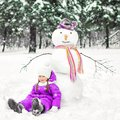 Child and snowman in a snow-covered Park. winter outdoor activities Royalty Free Stock Photo