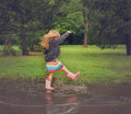 Child splashing in dirty mud puddle a little is a rain with pink rubber boots outside for a playful or happiness concept Royalty Free Stock Photography