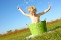 Child splashing water and bubbles in wash tub a happy young boy is playing outside a small green basin is bubble the air on a Royalty Free Stock Images