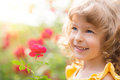 Child in spring happy with flower outdoors garden Royalty Free Stock Photos