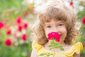 Child in spring happy with flower outdoors garden Royalty Free Stock Photo
