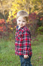 Child standing in fall foliage little boy and smiling over his shoulder with the the background Royalty Free Stock Photography