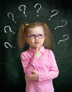 Child standing near school chalkboard with many question marks in eyeglasses blackboard Royalty Free Stock Image