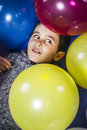 Child surrounded by balloons at a party sweet fun Stock Image
