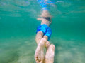 Child swimming seen from behind underwater Stock Photo