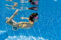 Child swimming underwater in pool Stock Photo