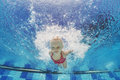 Child swimming underwater with splashes in the pool baby girl and diving fun jumping deep down active lifestyle water sports Royalty Free Stock Image