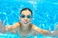 Child swims in pool underwater, funny happy girl in goggles has fun under water and makes bubbles, kid sport Royalty Free Stock Photo