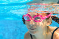 Child swims in pool underwater, happy active girl in goggles has fun in water, kid sport on family vacation Royalty Free Stock Photo
