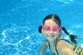 Child swims in pool underwater, happy active girl in goggles has fun in water Royalty Free Stock Photo