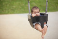 Child on a swing stock image of an infant he does not look to happy Stock Images