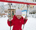 Child on swing in winter park Royalty Free Stock Photo