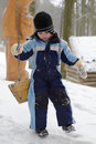Child on swing at winter playground with snow Stock Image