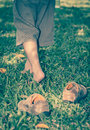 Child take off shoes child s foot learns to walk on grass leather close up reflexology massage kid relax in garden shallow depth Stock Photo