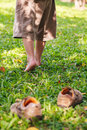 Child take off shoes child s foot learns to walk on grass leather close up reflexology massage kid relax in garden shallow depth Royalty Free Stock Images
