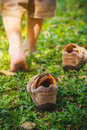 Child take off shoes child s foot learns to walk on grass leather reflexology massage kid relax in garden shallow depth of field Royalty Free Stock Photos