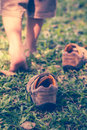 Child take off shoes child s foot learns to walk on green grass leather close up reflexology massage kid relax in garden shallow Stock Image