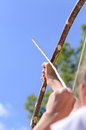 Child taking aim with an arrow over the shoulder closeup view of a young a bow and pointing it up towards the blue sky Royalty Free Stock Photo