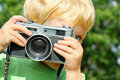 Child taking picture with vintage camera a young boy is pointing a at the viewer while playing outside Royalty Free Stock Photos