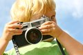 Child taking picture with vintage camera a young boy is pointing a at the viewer while playing outside Royalty Free Stock Photo