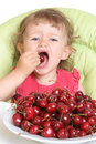Child tastes cherry Royalty Free Stock Photo