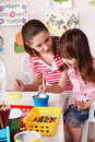 Child with teacher draw paints in play room. Royalty Free Stock Photo