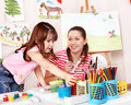 Child with teacher draw paints in play room. Stock Photo