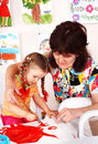 Child with teacher draw paints in playroom. Royalty Free Stock Photography