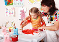Child with teacher draw paints in playroom. Royalty Free Stock Images