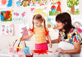 Child with teacher draw paints in playroom. Stock Photography