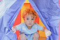 Child in a tent cute crouching looking out the coloured focus on the face Royalty Free Stock Photo