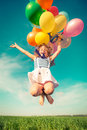 Child with toy balloons in spring field Royalty Free Stock Photo