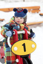 Child on toy motorcycle at playground in winter Stock Photography