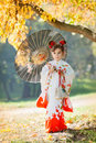 Child in traditional japanese kimono with umbrella against autumn yellow foliage Royalty Free Stock Photography