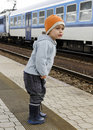 Child at train station waiting for a Royalty Free Stock Photo
