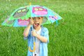 Child trapped in rain storm with umbrella a young is yelling as he holds a colorful the Royalty Free Stock Photography