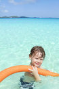 Child in tropical ocean pool swimming clear waters of a smiling and looking at the camera Stock Images