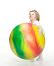 Child trying to carry huge fitball Stock Photography