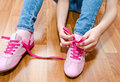 Child tying her shoes sitting on the floor at home closeup Stock Image